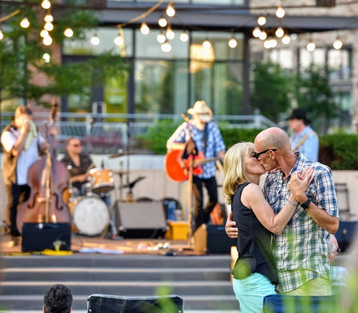 Couple kissing and dancing in front of live music with a stage and band in the background.